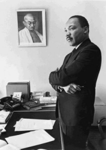 Martin Luther King, Jr. beside a picture of Gandhi; photograph © Bob Fitch
